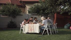 Familie, die im Garten isst stock footage