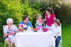 Familie, die im Garten zu Mittag isst Lizenzfreie Stockfotografie