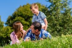 Familie, die im Gras auf Wiese, Sohnreiten auf Vati liegt Lizenzfreie Stockfotografie