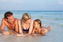 Familie, die im Meer auf tropischem Strandurlaub liegt Stockbilder