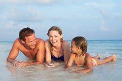 Familie, die im Meer auf tropischem Strandurlaub liegt Lizenzfreies Stockfoto