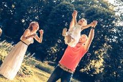 Familie, die im Park spielt Stockbilder