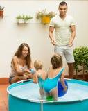 Familie, die im Pool an der Terrasse spielt Stockbild