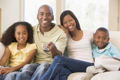 Familie, die im Raum mit Fernsteuerungs sitzt Lizenzfreies Stockfoto