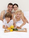 Familie, die im Schlafzimmer frühstückt stockfotografie