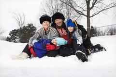 Familie, die im Schnee sitzt. Lizenzfreie Stockfotos