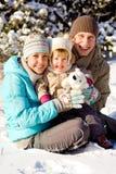 Familie, die im Schnee spielt Lizenzfreies Stockfoto