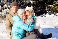 Familie, die im Schnee spielt Lizenzfreie Stockfotos