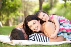 Familie, die im Sommer-Garten sich entspannt Stockfotografie