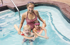 Familie, die im Swimmingpool spielt Lizenzfreie Stockbilder
