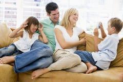 Familie, die im Wohnzimmer mit Digitalkamera sitzt Lizenzfreie Stockfotos