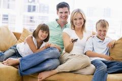 Familie, die im Wohnzimmer mit Fernsteuerungs sitzt Lizenzfreie Stockfotografie