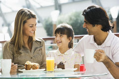 Familie, die Imbiß am Kaffee genießt
