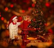 Familie die Kerstboom verfraait De vader en het jonge geitje vieren Kerstmis Royalty-vrije Stock Afbeeldingen