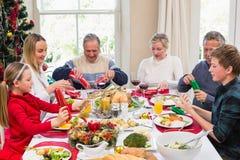 Familie die Kerstmiscrackers trekken bij de dinerlijst royalty-vrije stock foto