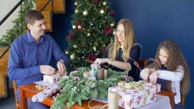 Familie die Kerstmisgiften in binnenlandse ruimte voorbereiden stock videobeelden