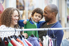 Familie, die Kleidung auf Schiene im Einkaufszentrum betrachtet lizenzfreie stockbilder