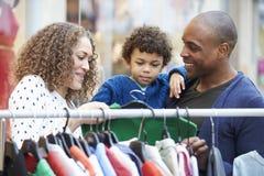 Familie, die Kleidung auf Schiene im Einkaufszentrum betrachtet stockbilder
