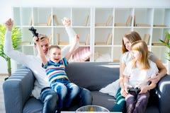 Familie, die Konsole spielt lizenzfreie stockfotos
