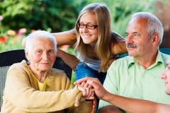 Familie, die kranke Großmutter im Pflegeheim besucht Lizenzfreie Stockfotos