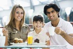 Familie, die Kuchen im Kaffee isst Lizenzfreies Stockfoto