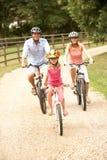Familie, die in Landschaft-tragende Sicherheit Helme einen Kreislauf durchmacht Lizenzfreie Stockfotos