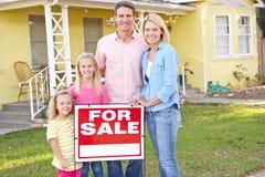 Familie die langs het Teken van de Verkoop buiten Huis betekenen stock fotografie
