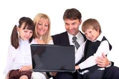 Familie die laptop bekijkt Stock Afbeelding