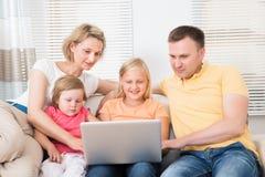 Familie die laptop op bank met behulp van Royalty-vrije Stock Foto's