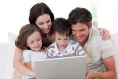 Familie die laptop op de bank met behulp van Stock Foto's