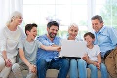 Familie die laptop op een bank met behulp van stock afbeeldingen