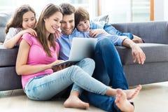 Familie die Laptop thuis met behulp van Stock Fotografie