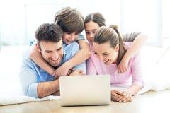 Familie die Laptop thuis met behulp van Stock Foto's