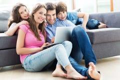 Familie die Laptop thuis met behulp van Stock Afbeelding