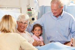 Familie, die älteren weiblichen Patienten im Krankenhaus-Bett besucht Lizenzfreies Stockfoto