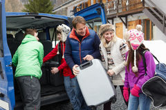 Familie, die Luggage From Van Outside Chalet aus dem Programm nimmt Stockfotos