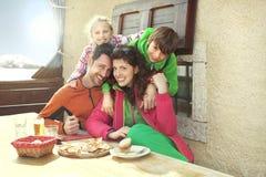 Familie die lunch in een chalet in berg hebben stock foto