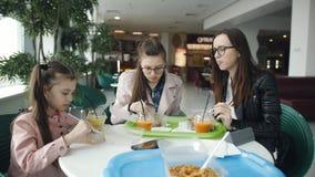 Familie die lunch samen in een koffie hebben Moeder en twee dochters in een koffie die noedels eten en vers sap drinken stock videobeelden