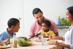 Familie die Maaltijd samen thuis eten stock afbeelding