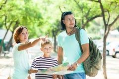 Familie die manier zoeken bij kaart Royalty-vrije Stock Foto's
