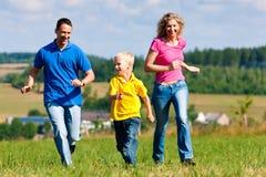 Familie, die Marke auf Wiese am Sommer spielt Stockfotos