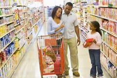 Familie die meningsverschil in supermarkt heeft stock afbeelding