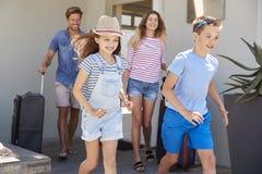 Familie die met Bagage Huis voor Vakantie verlaten stock foto's