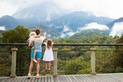 Familie die met jonge geitjes berg bekijken stock afbeeldingen