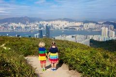 Familie die met jonge geitjes in Hong Kong-bergen wandelen Mooi landschap met heuvels, overzeese en stadswolkenkrabbers in Hong K stock afbeelding