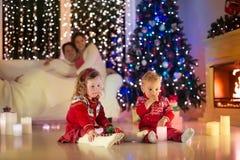 Familie die met jonge geitjes Kerstmis thuis vieren stock afbeeldingen