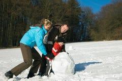 Familie die met jonge geitjes sneeuwman maakt Stock Foto
