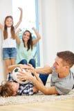 Familie die met voetbalbal stoeien Stock Afbeeldingen