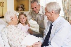 Familie, die mit älterer Frau im Krankenhaus sitzt Stockbilder