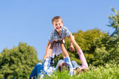 Familie, die mit dem Sohn liegt im Gras auf Wiese spielt Stockbild